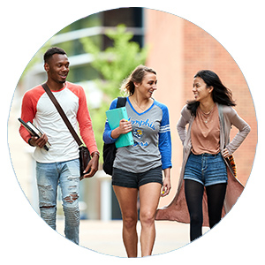 three students walking and talking on campus