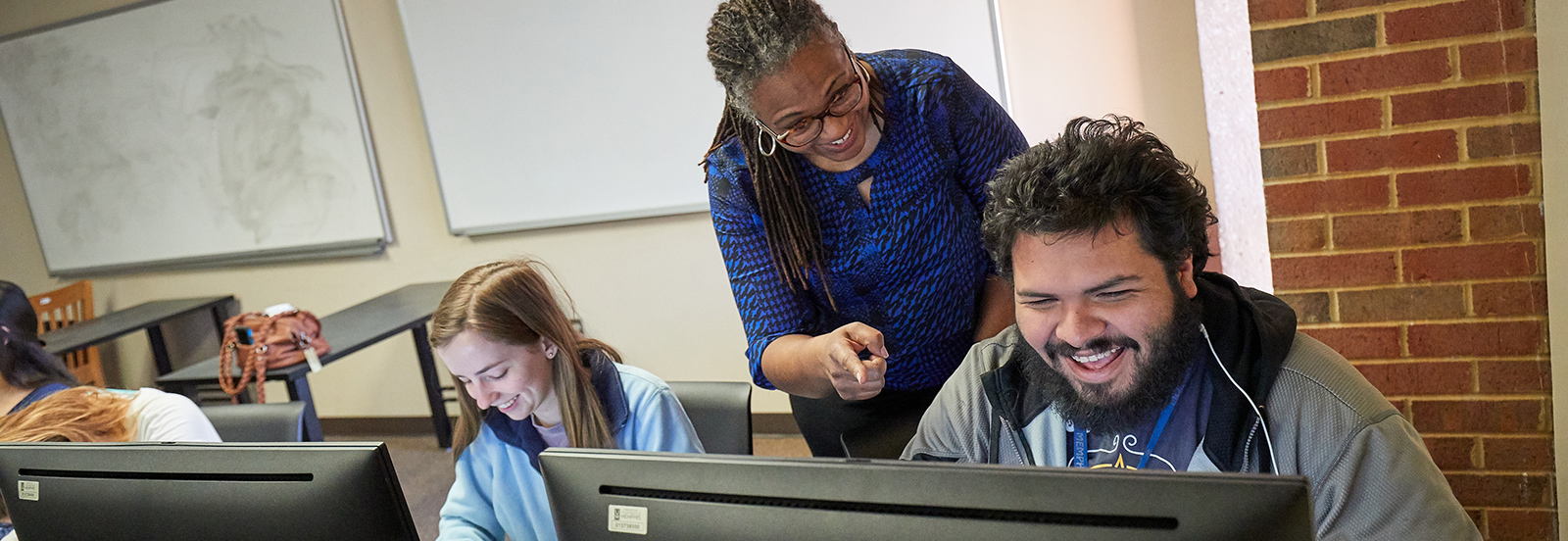 Teacher helping students at computer