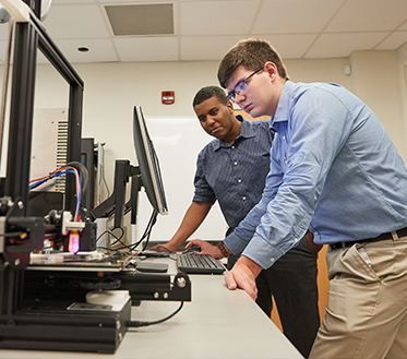 two male students lean over looking at computer