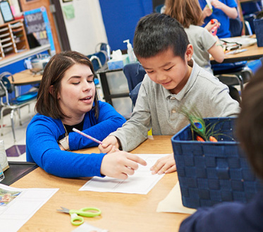 teacher helps young student in classroom