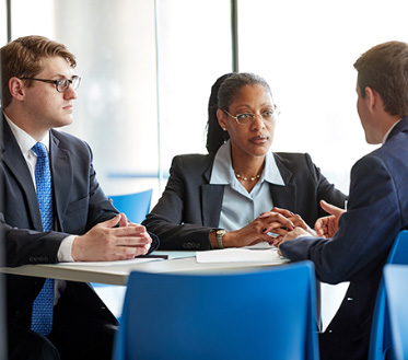 group of professionals wearing suits talks around a table