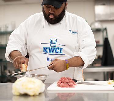 chef in kitchen wearing KWCI apron