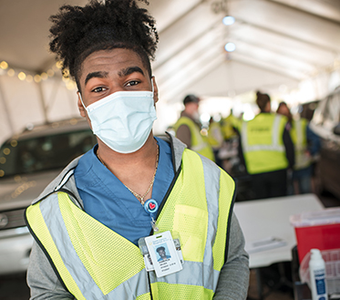 student wearing mask volunteering at vaccine site