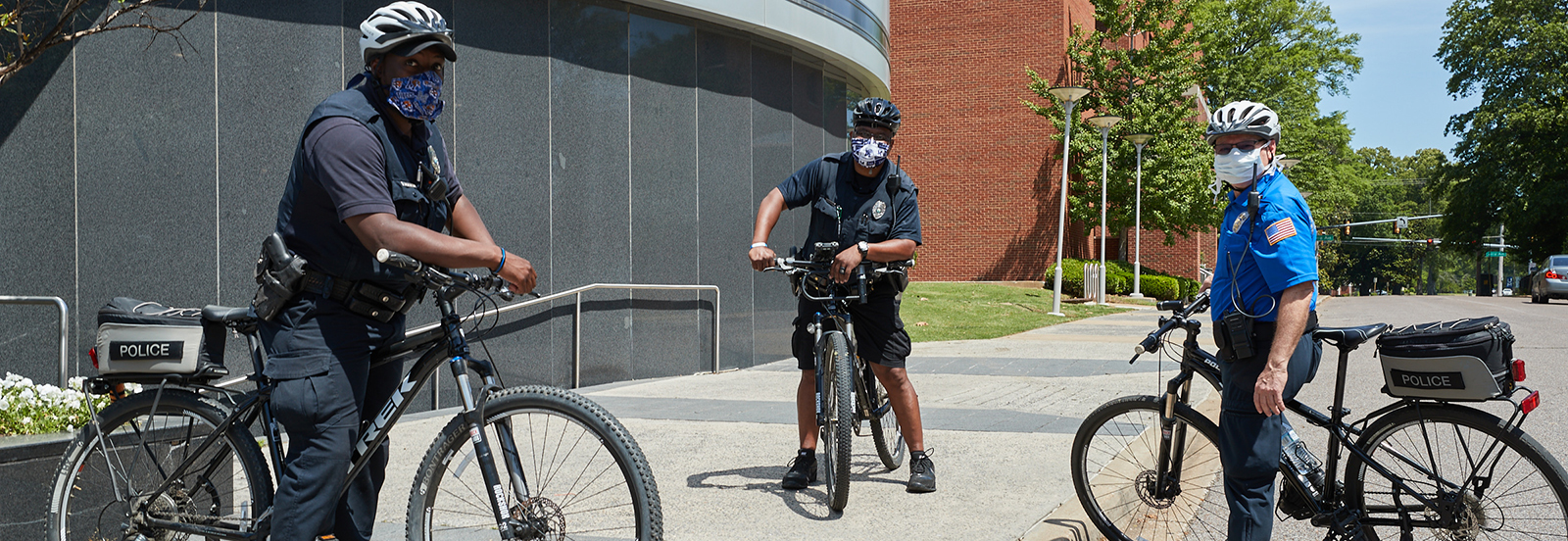 Police Officers patrolling on bike pose for a picture wearing their masks