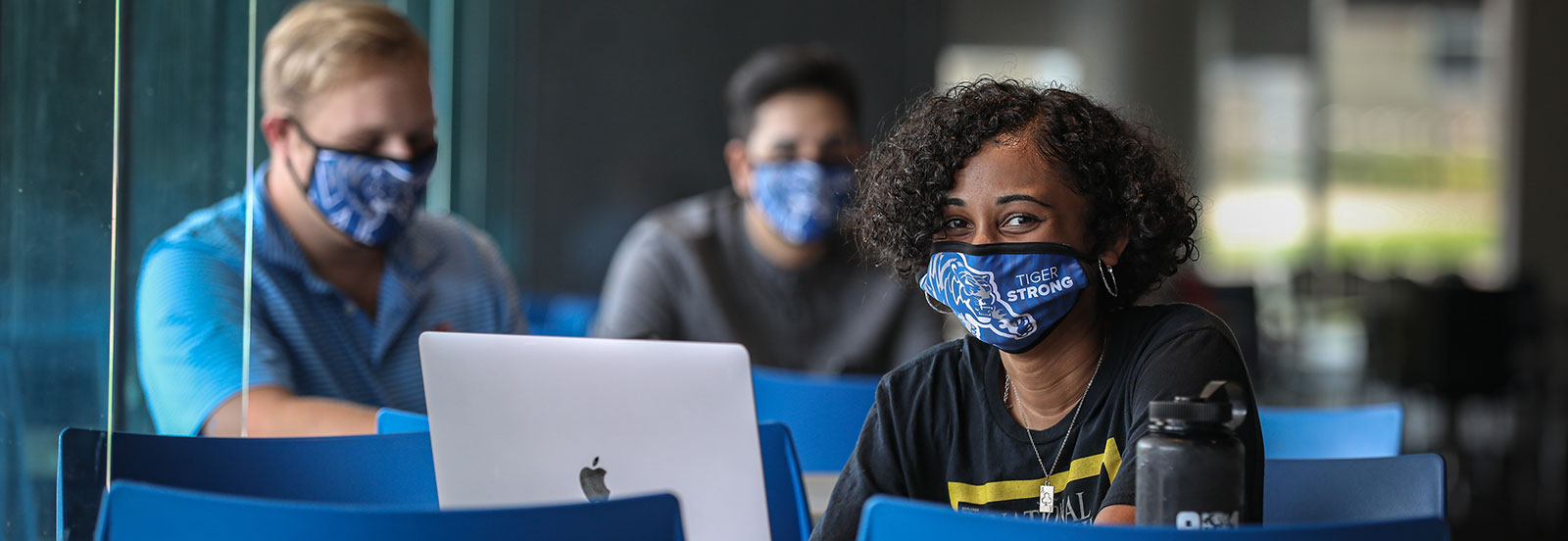 "student wearing face covering with UofM athletic logo and ""Tiger Strong""; 2 students distanced in the background with matching face covering"