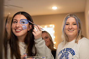female students putting on gameday makeup in dorm