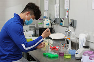 researcher in lab wearing a mask