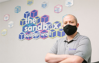 employee wearing a mask stands in front of The Sandbox sign