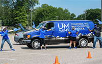 UofM Alumni Association staff socially distanced in front of the UofM van