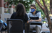 two students sit at outdoor table wearing a mask