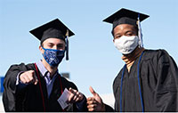 two male graduates wearing face masks at commencement