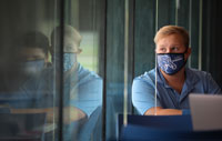 student wearing mask sitting at table