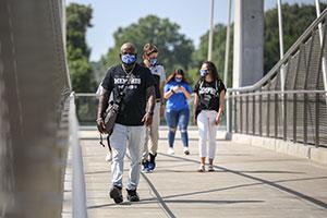 students wearing face coverings walking across the bridge