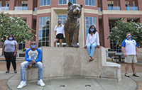 students wearing mask socially disctanced around bronze tiger statue