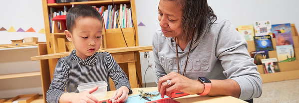 A teacher works with a preschool student