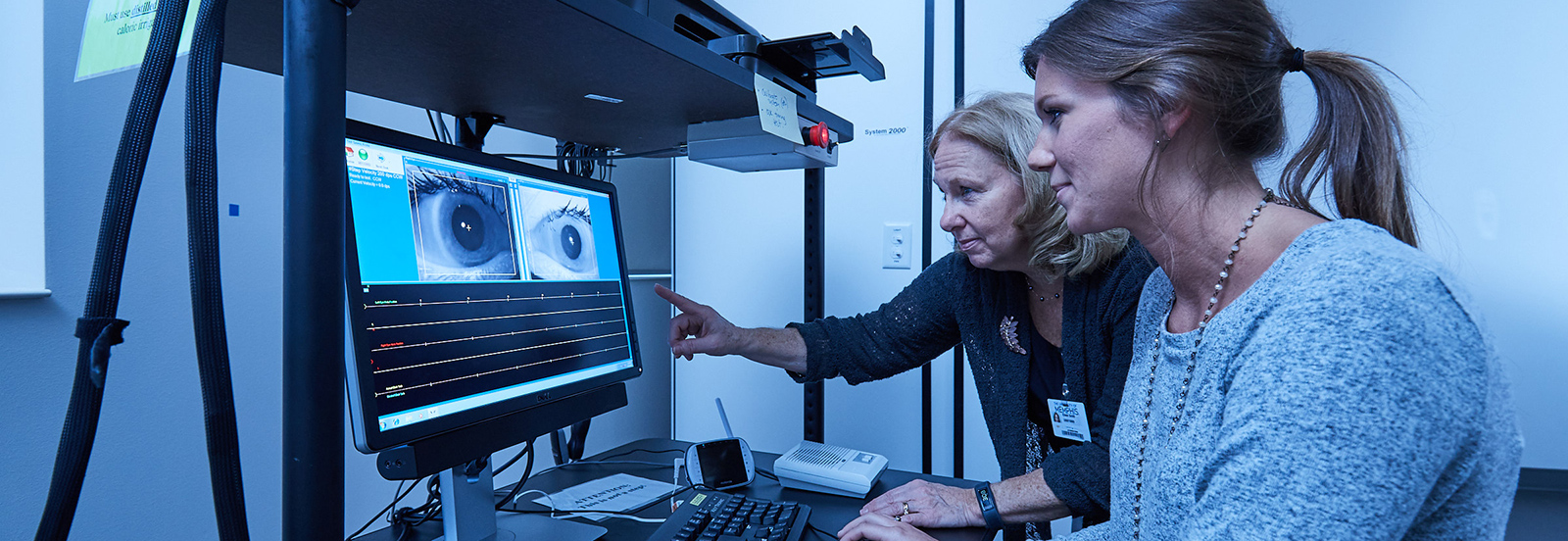 student and faculty member looking at eye research