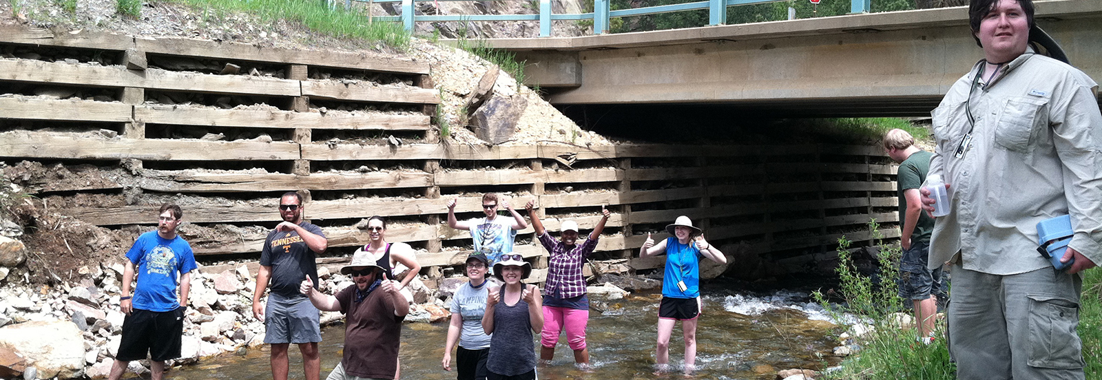 ESCI 4622, Geology Field Camp, students measuring stream discharge and cooling off at Lead, South Dakota.