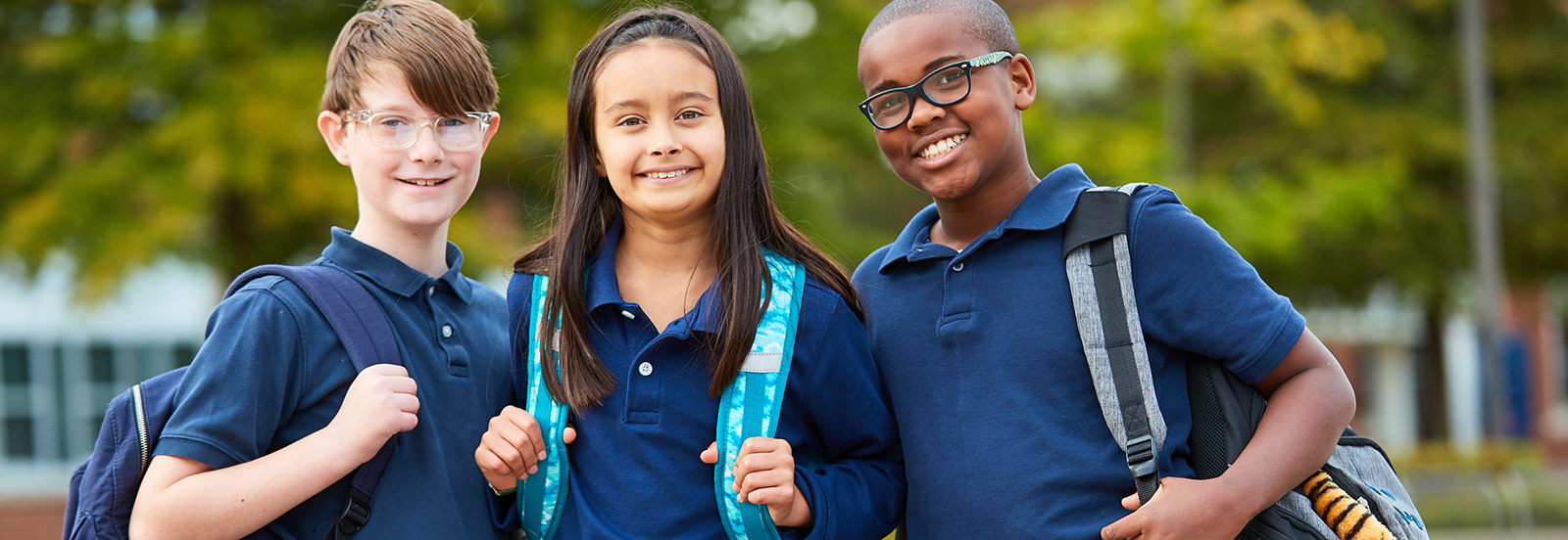 three students posing with backpacks