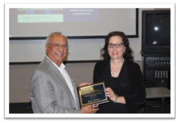 Dr. Kelly Mollica (right) receiving the George Johnson Fellow Award for Teaching from Dean Rajiv Grover