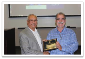 Nap Overton (right) receiving the George Johnson Fellow Award for Teaching from Dean Rajiv Grover