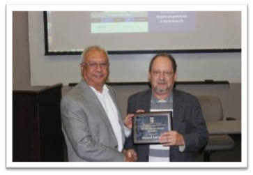 Dr. Michael Cervetti (right) receiving the George Johnson Fellow Award for Teaching from Dean Rajiv Grover