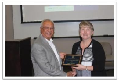 Dean Grover presenting the George Johnson Staff Award to Carol Thomas (right)