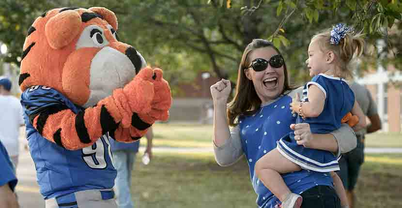 Tiger mascot giving thumbs up to little girl and mother