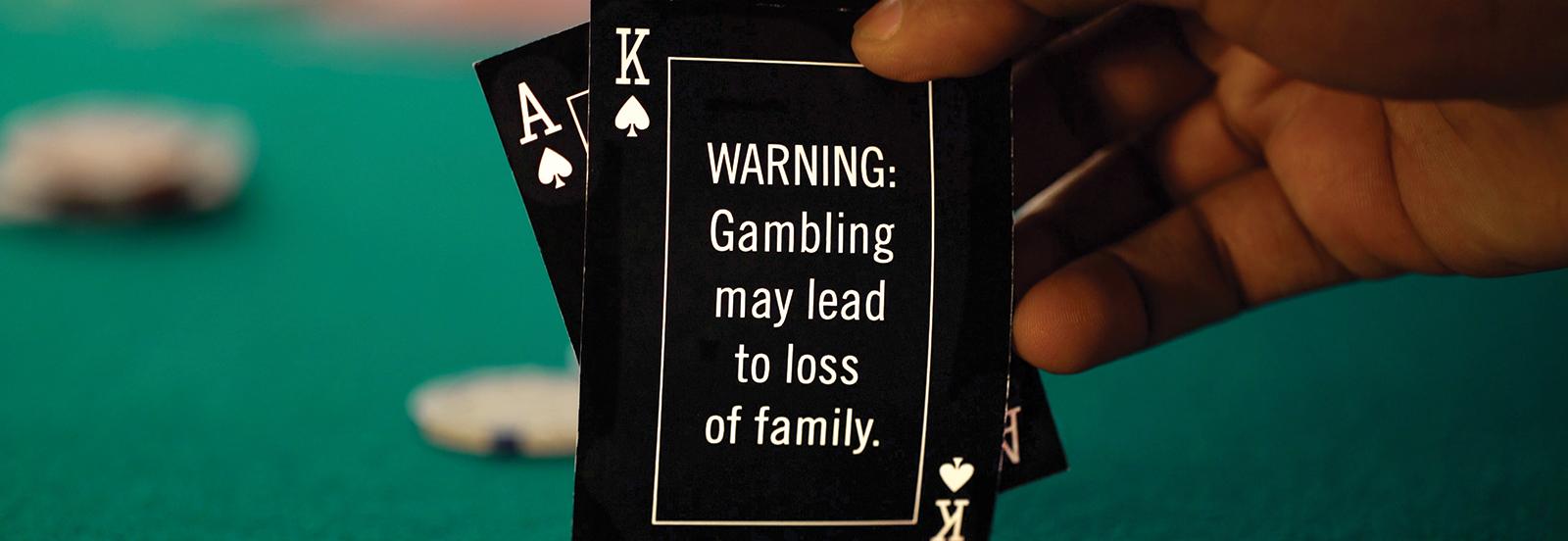 "poker card reads ""Warning: Gambling may lead to loss of family."""