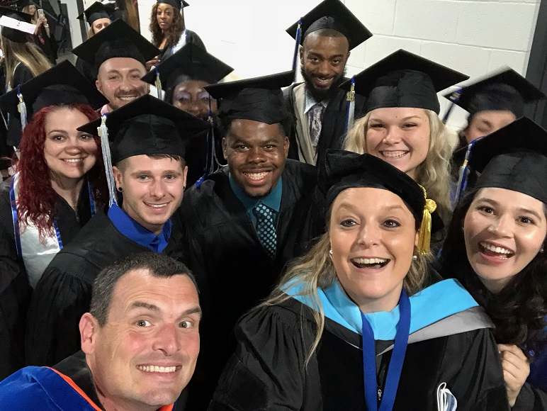 Dr. Niki Bray and Dr. Todd Layne take a selfie with students in line for commencement.