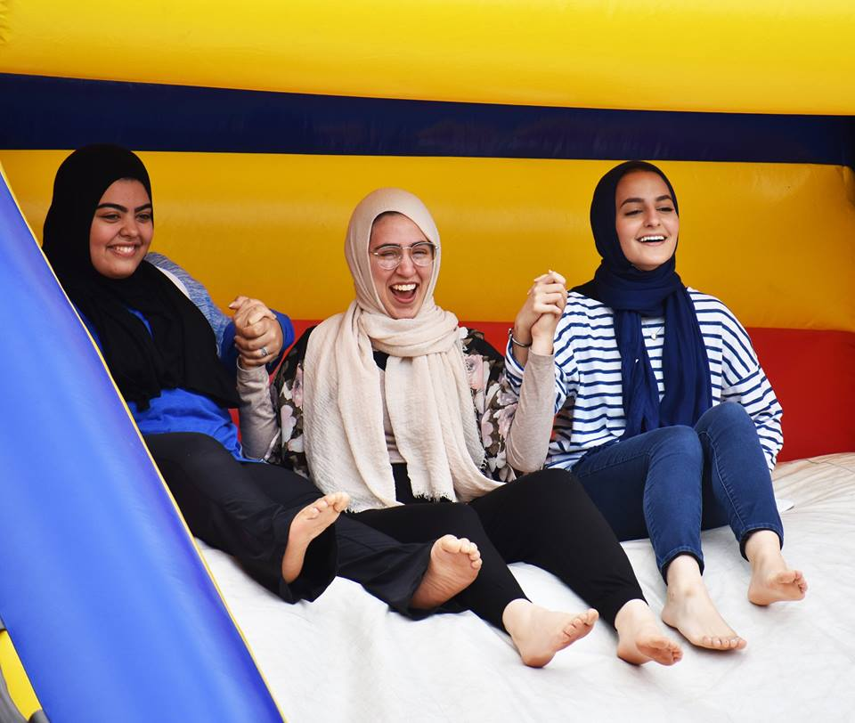 U of M Students slide down bounce house together
