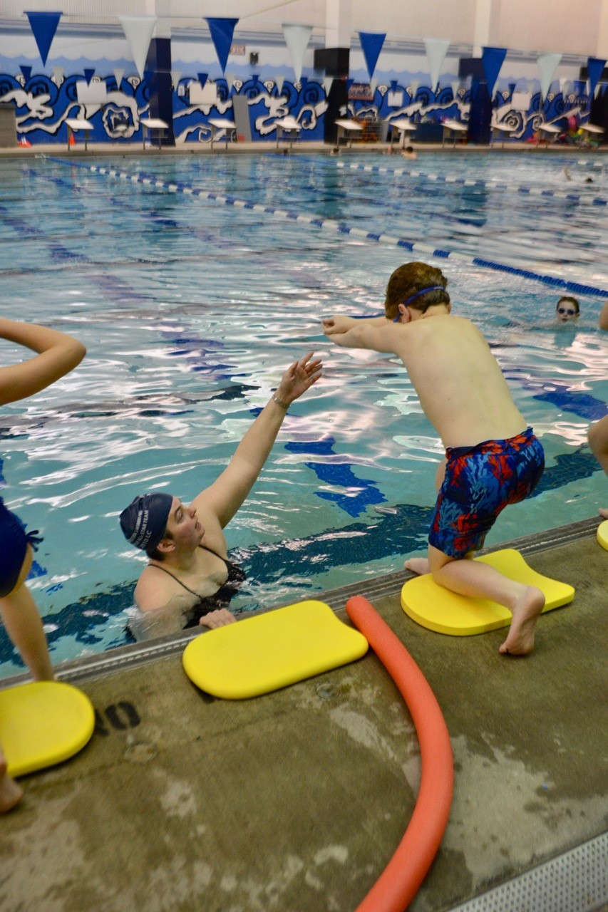 UM student teaches a Campus School 5th grader to dive safely into pool.