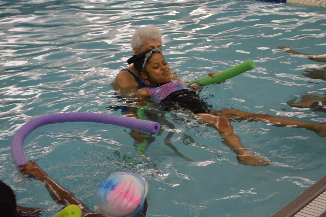 SHS Instructor teaches a Campus School 5th grader to float in pool.