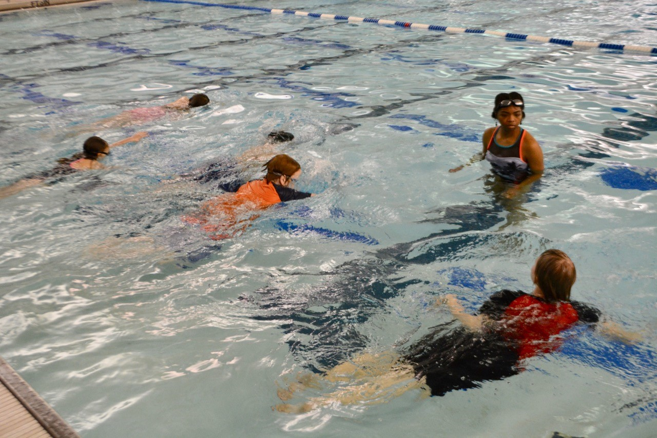 UM student teaches a group of Campus School 5th graders to swim.