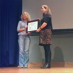 Awards ceremony, teacher receiving certificate