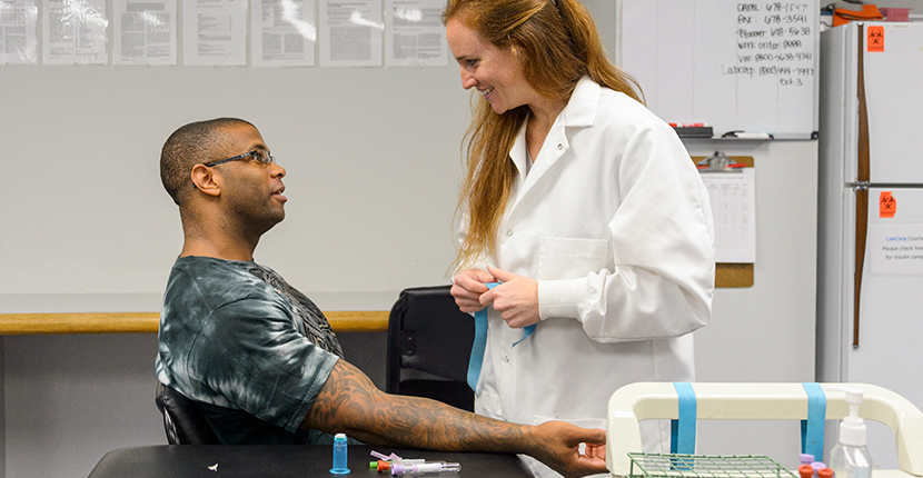 Human Performance Center worker performs a blood draw on client