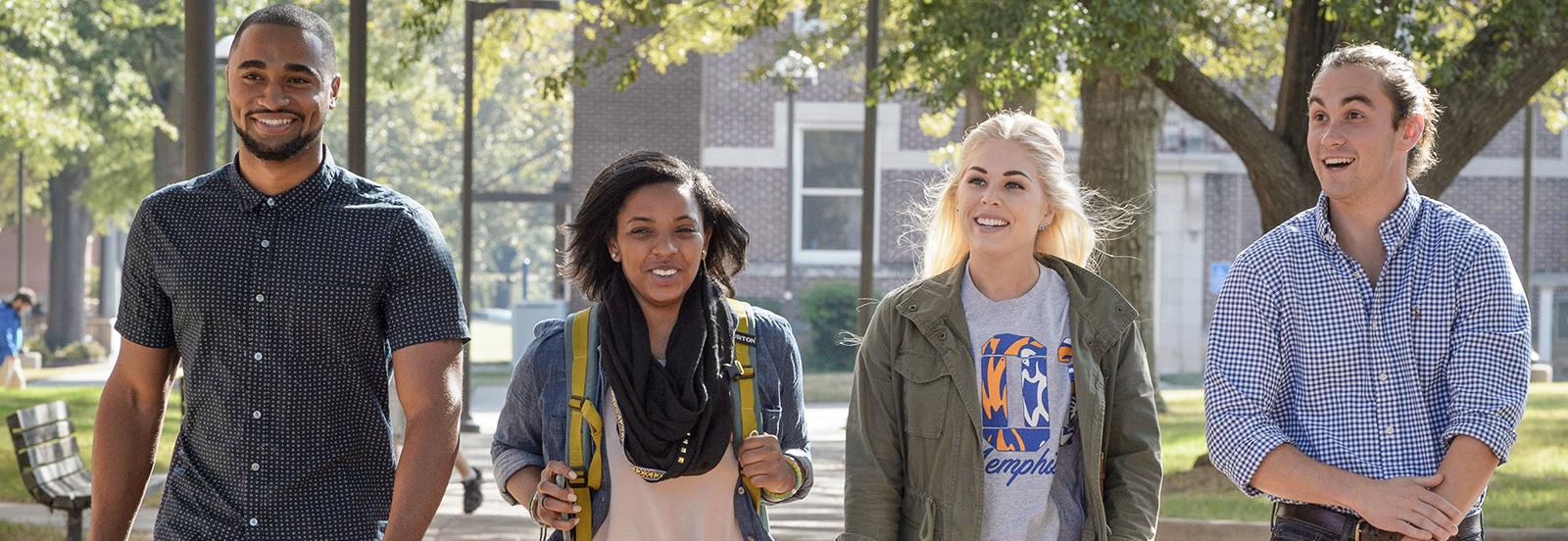 four students walking through campus