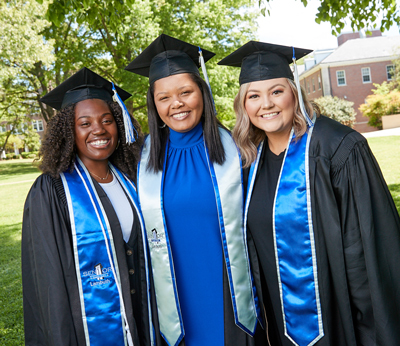 three graduates after baccalaureate ceremony