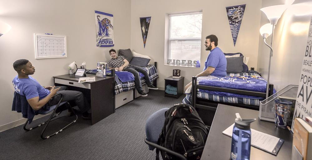 Three male students chatting, relaxing, two lounging on separate beds, one sitting with laptop at a desk in a Living Learning Complex double bedroom consisting of UofM blue and gray logo signage banners on the wall.