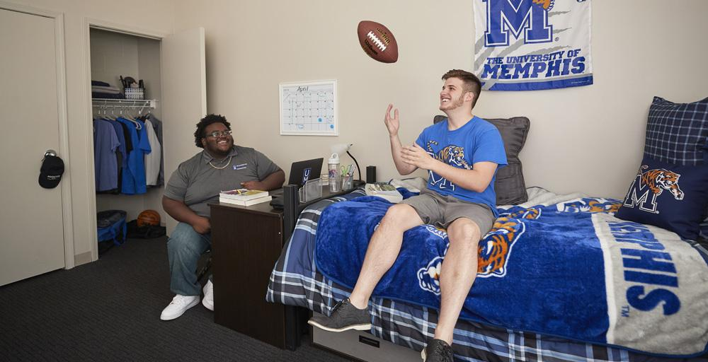 Two students relaxing, one tossing football in the air sitting on a bed within Living Learning Complex with UofM blue and gray paraphernalia within the room; bed cover, signage on the wall, Tiger logo pillow.