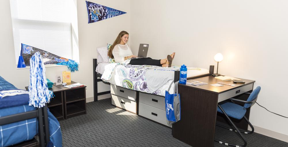 One female student sitting on bed studying with UofM logo paraphernalia throughout; blue and gray tenant on the wall, pompom hanging from bedpost in a Living Learning Complex double bedroom.