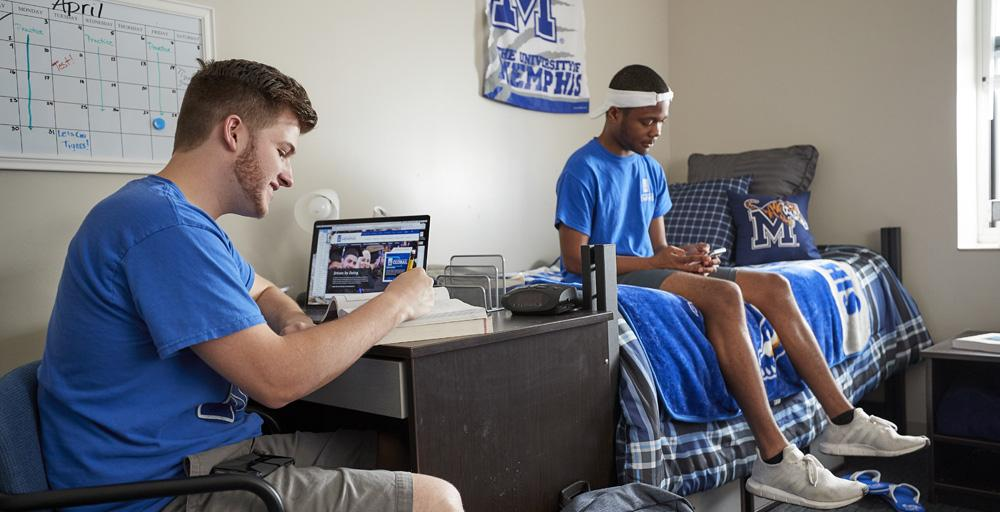 Two male students lounging in Living Learning Complex (LLC) double bed room with UofM blue and gray paraphernalia throughout; students wearing blue t-shirts, Tiger Athletics M-logo on the wall, calendar post on the wall.