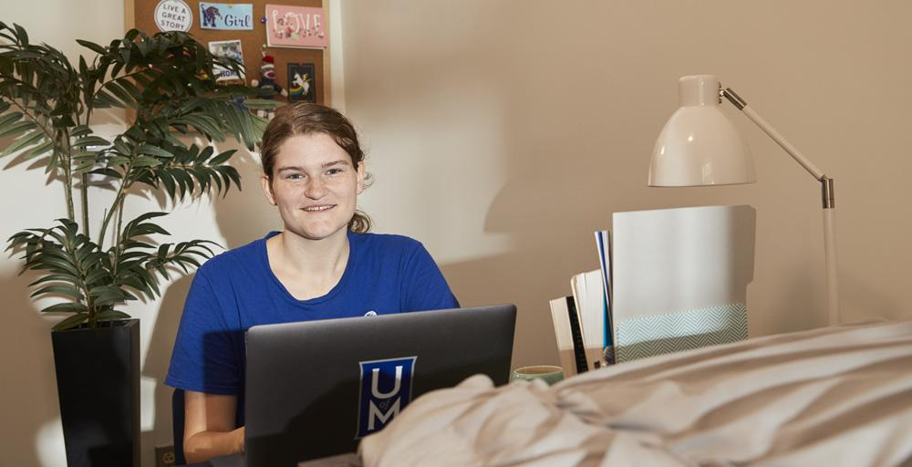 student with computer desktop in dorm room