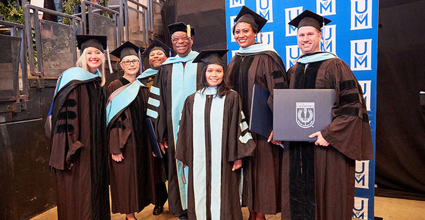 students and faculty in commencement robes