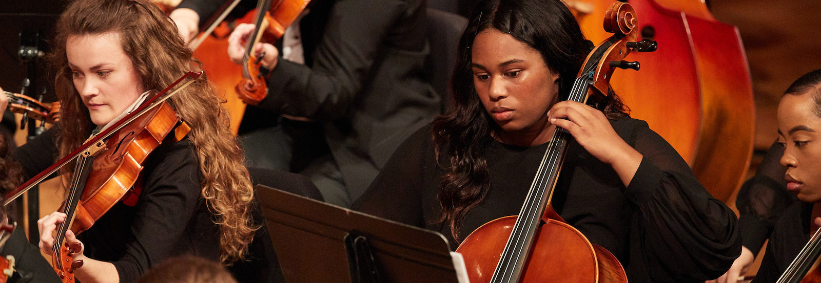 Students playing viola and cello in the orchestra.