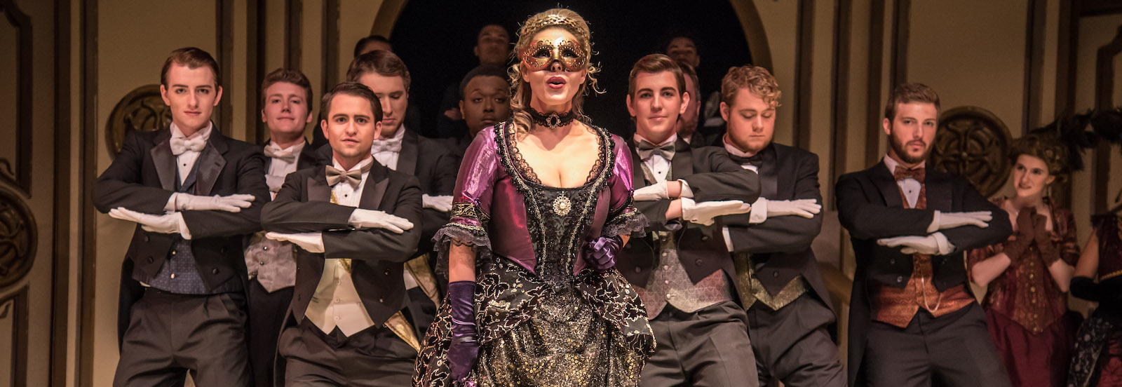 A scene from the opera Die Fledermaus, with a woman in an ornate gown and mask centered in front of a group of men in tuxedoes.