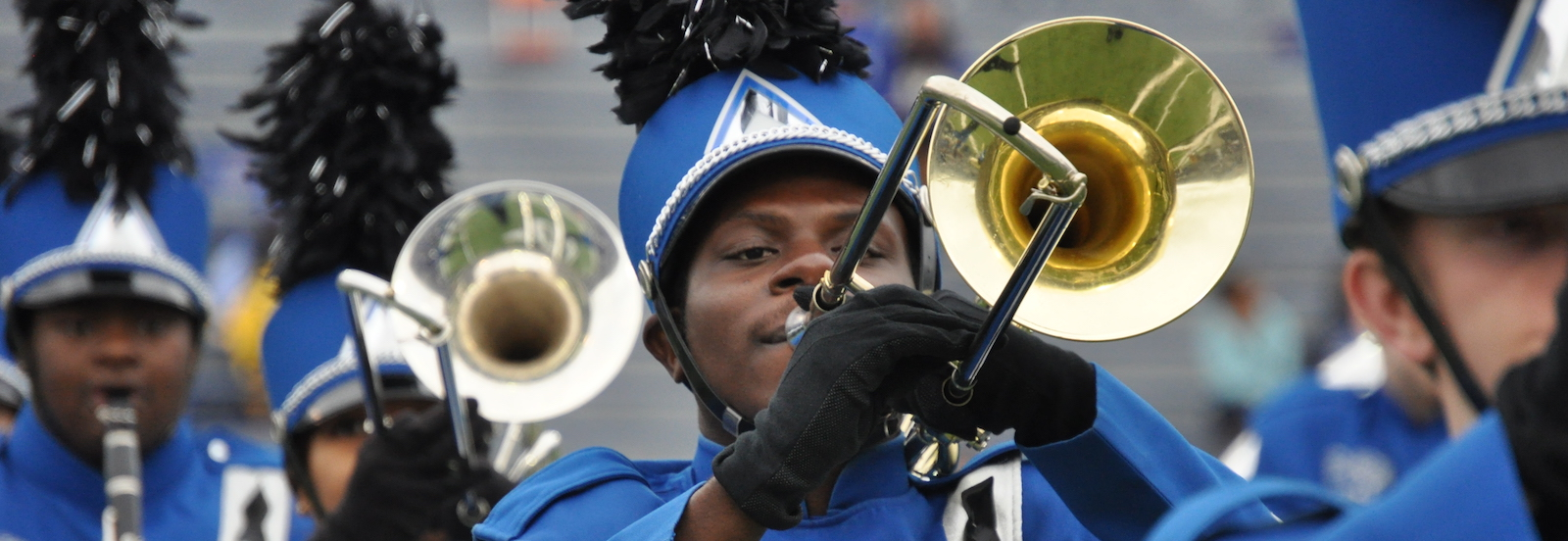 Members of the Mighty Sound of the South in bright blue marching uniforms playing trombone.