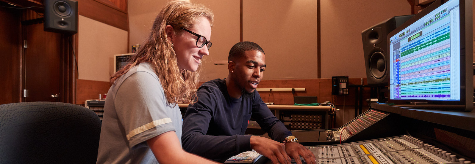 Two music industry majors working at a mixing board in a recording studio