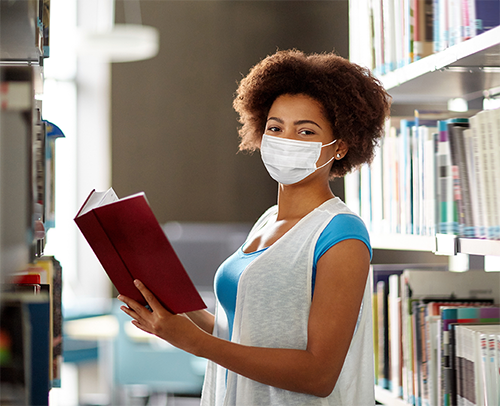 Student in library holding a book, wearing mask