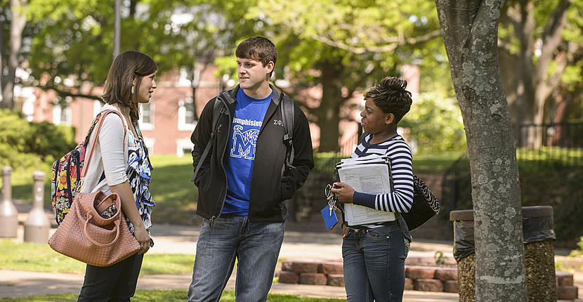 three students chatting on campus