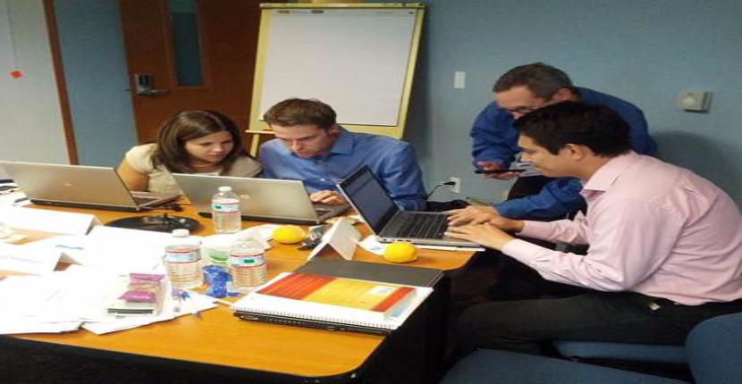 four students at laptops analyzing information sitting around table meeting